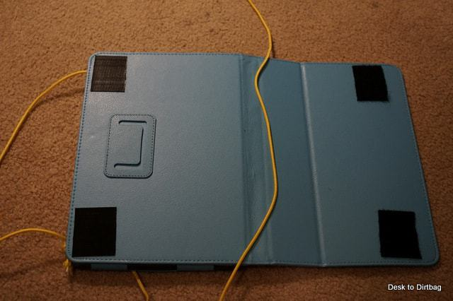 Back of the tablet case with sticky velcro and the cord the lays in the fold.