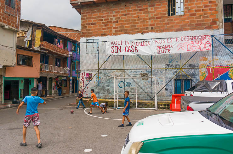 Children playing soccer on a tiny lot with a sign of the resistance for Moravia Medellin